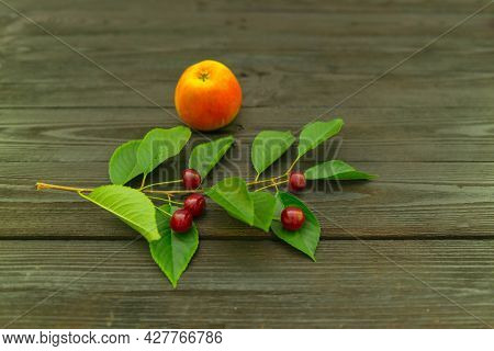 An Apple And Cherry Fruit Placed On A Dark Wooden Background. An Apple And Cherry Fruit Placed On A