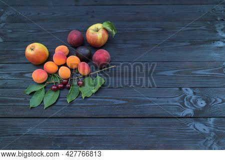 The Fruit Is Placed On A Dark Wooden Background.\\nripe Fruit Placed On A Wooden, Painted Black Back