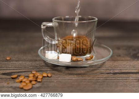 Pouring Boiling Water Over Coffee.\na Transparent Glass Cup On A Saucer Standing On A Black, Wooden