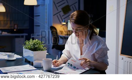 Workaholic Businesswoman Working In Company Office Meeting Room Writing Financial Statistics While L