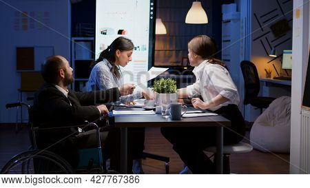 Overworked Paralyzed Disabled Entrepreneur Man In Wheelchair Sitting At Desk Overworking In Company