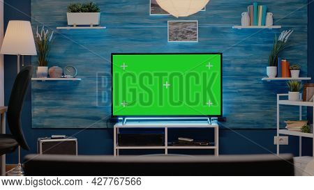 Empty Room With Green Screen On Television In Living Room At Modern Home. Tv Display With Mockup Tem