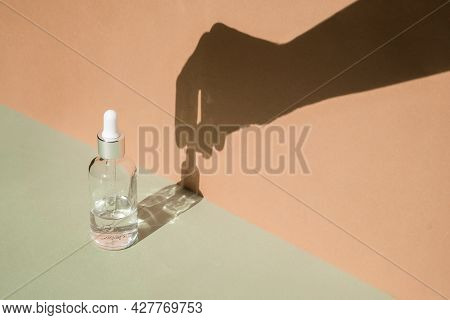 Dropper Glass Bottle With Hand Shadow On Wall. Body Treatment And Spa. Natural Beauty Products. Eco