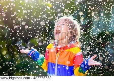 Child Playing In Autumn Rain. Kid With Umbrella.