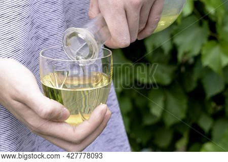 The Winemaker Pours White Wine From A Bottle Into A Glass