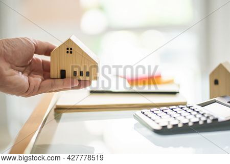 Human Hand Holding Wooden House Mock Up And Giving Or Put It On The Desk With Blurred Calculator. Fi