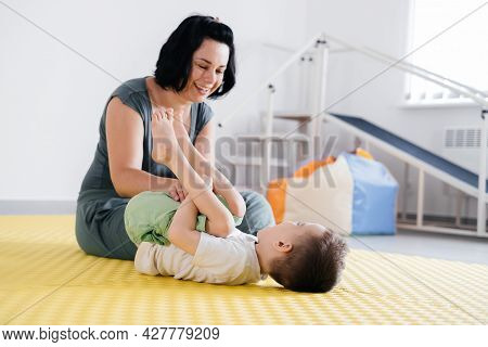 Rehabilitation Of Child With Cerebral Palsy In Special Center. Mother Doing Physical Exercises And H