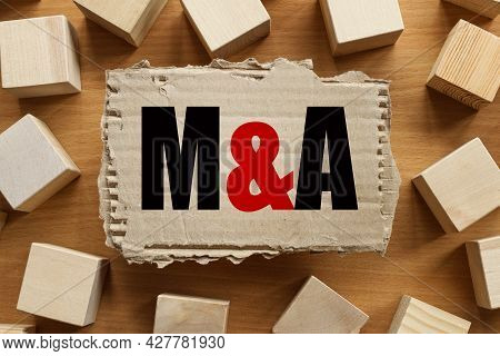 M And A Merger And Acquisition. Text On Torn Cardboard On Wood Cubes Background