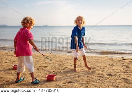 Kids Blow Bubbles At Tropical Beach. Child Blowing Soap Bubble Playing At Sea. Family Summer Vacatio