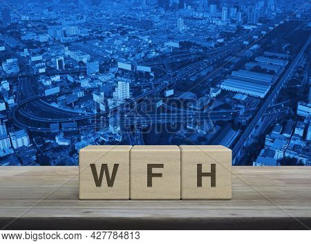Wfh Letter On Block Cubes On Wooden Table Over Modern City Tower, Street, Expressway And Skyscraper,
