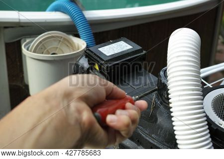 A Hand With A Tool Unscrewing Electric Water Pump