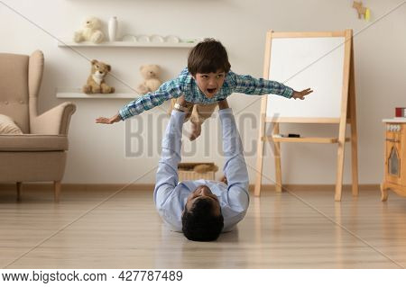 Loving Indian Father Lifting Excited Son Pretending Flying On Floor