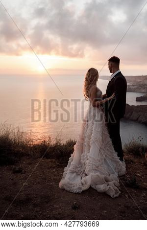 A Beautiful Bride And Groom On Their Wedding Day Walk Along The Rocky Coast By The Sea.young Couple