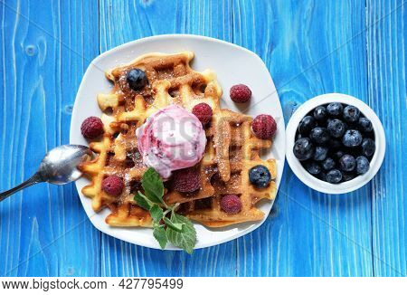 Belgian waffles with fresh berries and ice cream over blue wooden background, close up