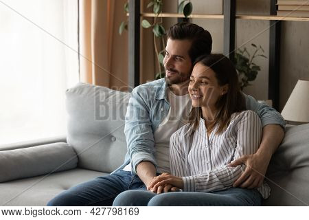 Loving Couple Relax On Sofa Cuddling Daydreaming Looking Into Distance