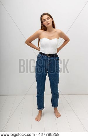 Young Attractive Caucasian Woman With Long Brown Hair In Corset, Blue Jeans On White Studio Backgrou