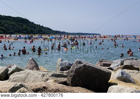 Sea Coast In Summer - Stones Strengthening Shore And Holidaymakers Relaxing In The Sea Water