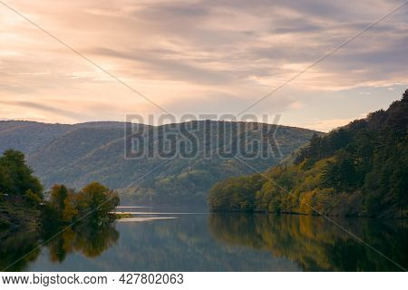Beautiful Evening Scenery With Lake. Glowing Clouds Reflecting On The Water Surface. Wonderful Autum