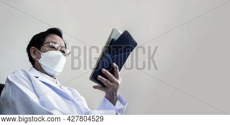 Asian Senior Elder Woman Doctor Wearing Mask Looking At Tablet Screen Diagnose Patient Data Informat