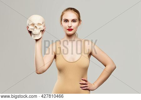 Attractive Blonde Holds A Skull In Her Hands. The Concept Of Photography Is Suitable In The Field Of