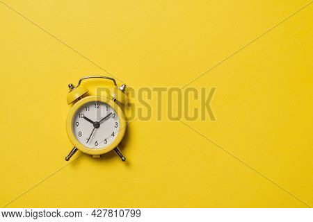 Yellow Alarm Clock On A Yellow Background. Copy Space. Time Concept. Copy Space.