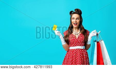 Smiling Young Pinup Woman Holding Gift Bags And Credit Card, Looking At Blank Space On Blue Studio B