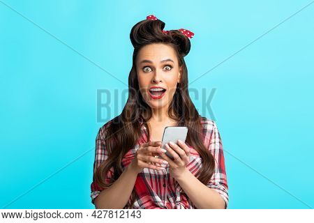 Excited Young Pinup Woman In Retro Outfit Using Smartphone Over Blue Studio Background