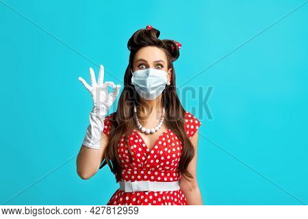 Portrait Of Pinup Woman In Retro Outfit Wearing Face Mask To Prevent Covid, Showing Okay Gesture Ove
