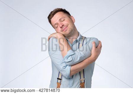 Pleased Caucasian Man Hugs Himself, Has High Self Esteem, Feels Comfort
