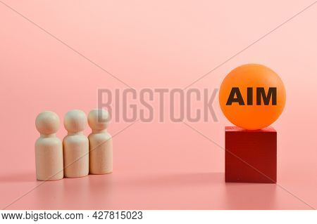 Group Of People Standing In Front Of The Word Aim. Goals Concept
