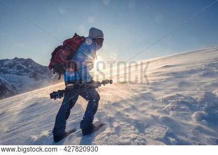 Backpacker Man Mountaineering On Snow Mountain With Sunray In Blizzard At Norway