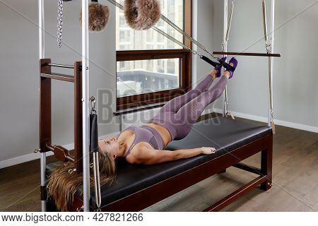Pilates Instructor On The Cadilak Reformer, A Woman Trainer In Excellent Shape Works On A Modern Ref