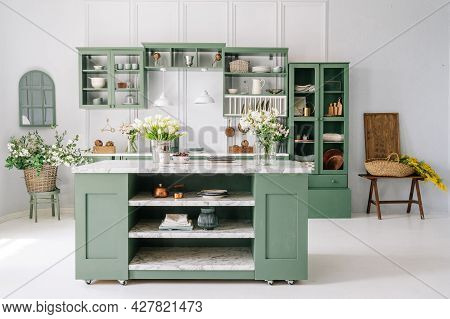 Kitchen With Island, Decor With Green Furniture, White Walls And Floor, Counter With Flowers In Glas