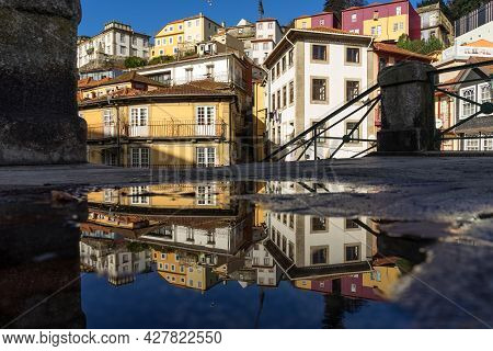 Porto, Portugal - December 01, 2019: Typical Houses Of Porto Reflected In A Puddle.