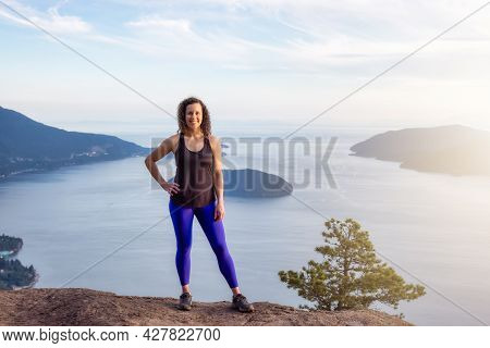 Adventurous Caucasian Adult Woman Hiking On Top Of A Mountain During A Colorful Sunny Summer Day. Tu