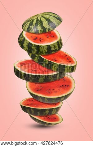 Ripe Watermelon Cut Into Pieces Flying In The Air On A Trendy Colored Background.