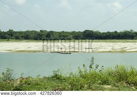 The Gorai River With Blue Water And Surrounded By Greenery, Some Boat Floating On The Water Fisherme