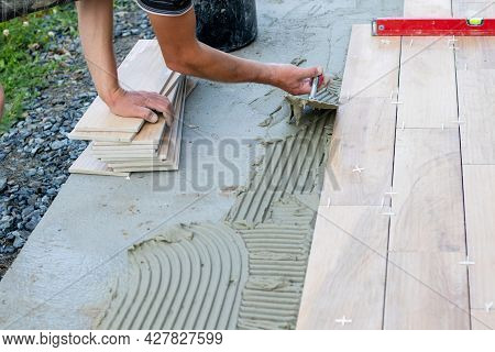 The Hands Of The Professional Tiler Lying Or Installing Modern, Ceramic Tile Above Cement On The Gar