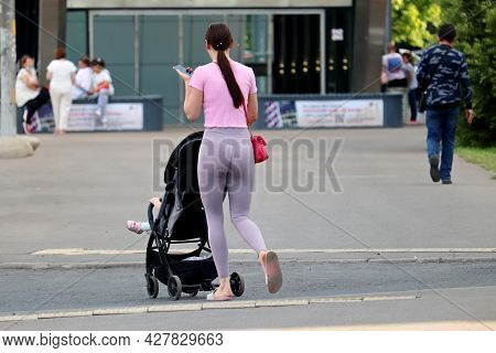 Slim Woman In Leggings With A Baby Stroller Crossing The City Street With Smartphone In Hand. Concep