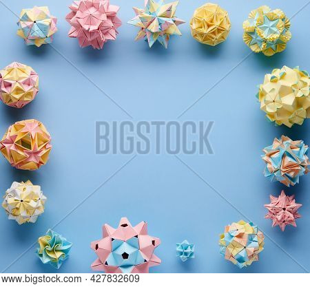Set Of Multicolor Handmade Modular Origami Balls Or Kusudama Isolated On Blue Background. Visual Art