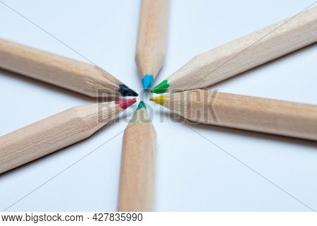 Close-up Of A Colorful Wooden Pencils Arranged In A Symmetrical Radial Star Shape. White Background.