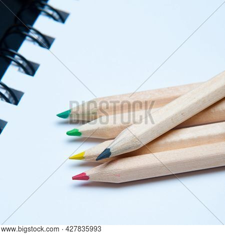 Close-up Of Five Colorful Wooden Pencils Arranged Over A White Notepad. School Material
