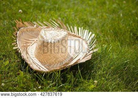 Farmer's Yellow Straw Hat In The Grass. Rural Symbol.