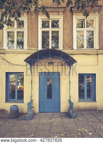 Porch And Front Door Painted In Bright Blue Color. Vintage Doorway And Framed Windows Of Building Ex