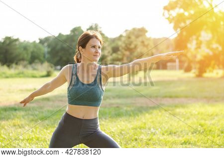 A Woman Goes In For Sports In Nature. Sportive Young Woman Practices Yoga In The Park. Woman Athlete