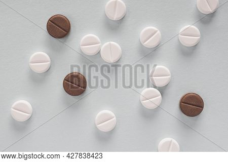White And Brown Pills Lie On A Gray Paper Surface. Close-up. Light Background Or Backdrop About Medi