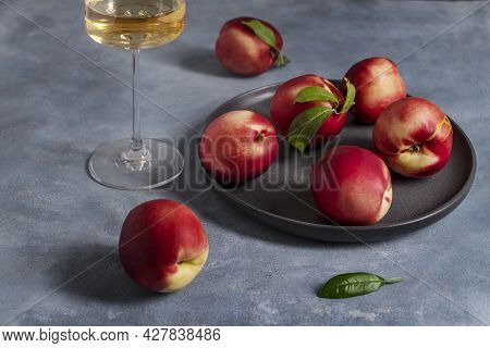 Several Ripe Peaches Or Nectarines On A Black Ceramic Plate And A Glass Of White Wine Sit On A Blue