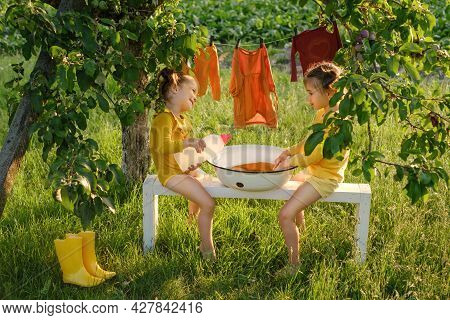 Two Little Girls Sisters Wash Clothes In A Basin In The Garden With Washing Liquid Detergent From A