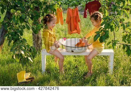 Children Are Sitting On A Bench And Wash Clothes In An Old Basin With A Liquid Hypoallergenic Gel Fo
