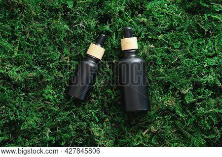 Black Dropper Serum Bottles On Moss Background. Luxury Cosmetics Design, Branding. Flat Lay, Top Vie